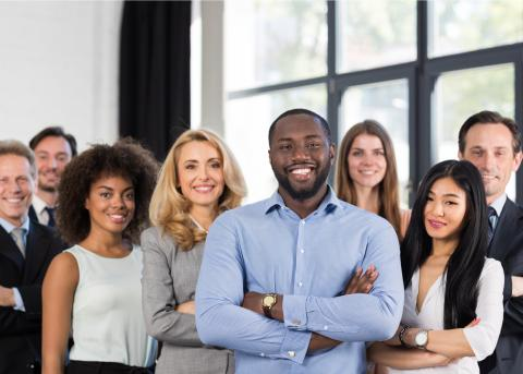 A group of smiling, confident-looking and diverse business professionals.