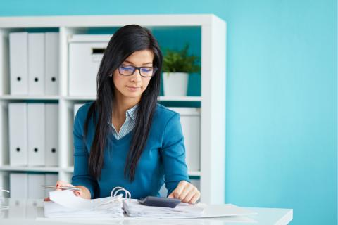 Young woman with glasses and a blue sweater sitting at a desk and reviewing financial documents.