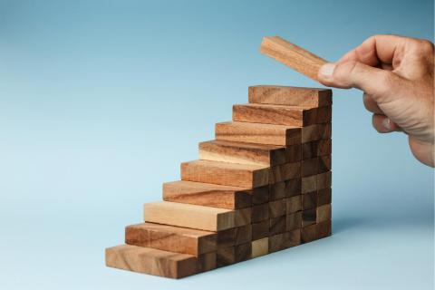 Wooden blocks arranged as steps, with a hand placing a block at the top step.