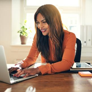 Young woman in orange blouse sitting in a home office, typing on a laptop and smiling.